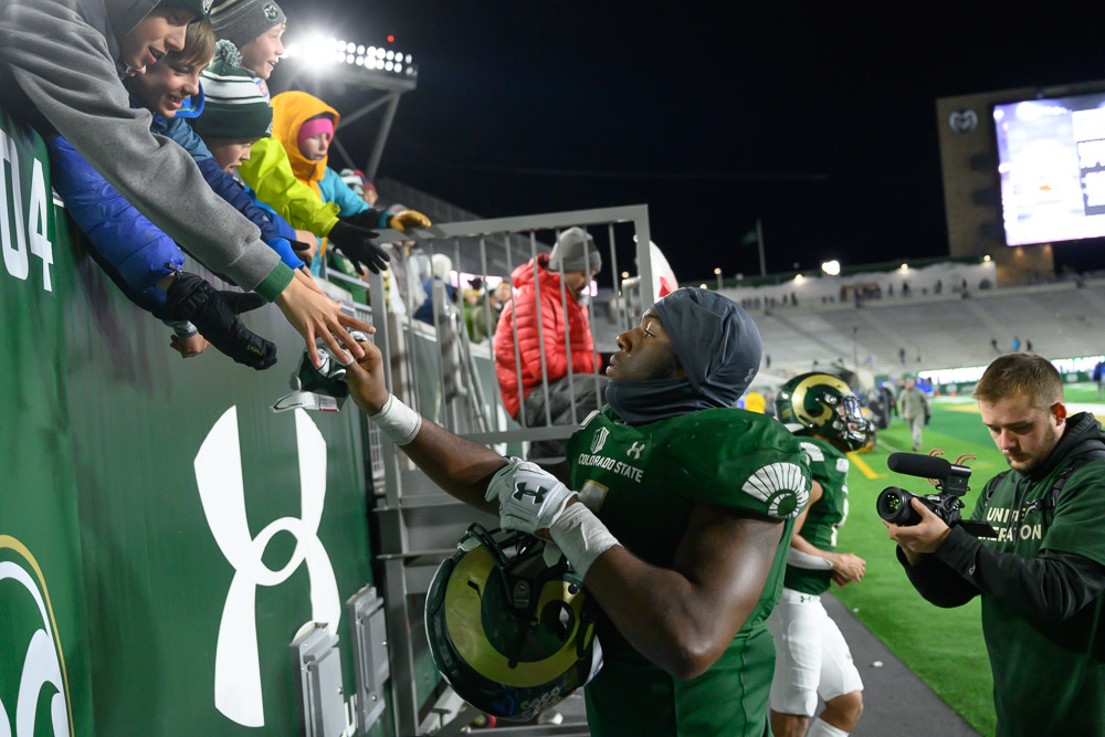 A CSU football player handing something to a fan in the stands