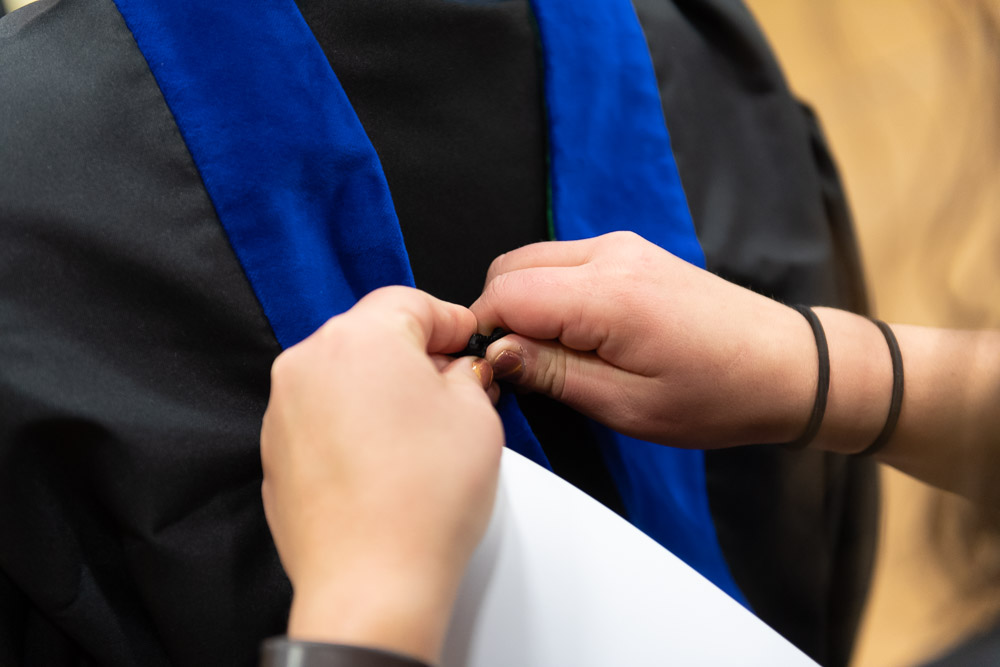 A person pinning a hood on a graduate's robe