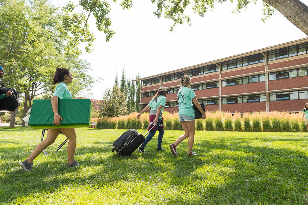 Students carrying boxes and pulling suitcases, helping new students move into the residence halls